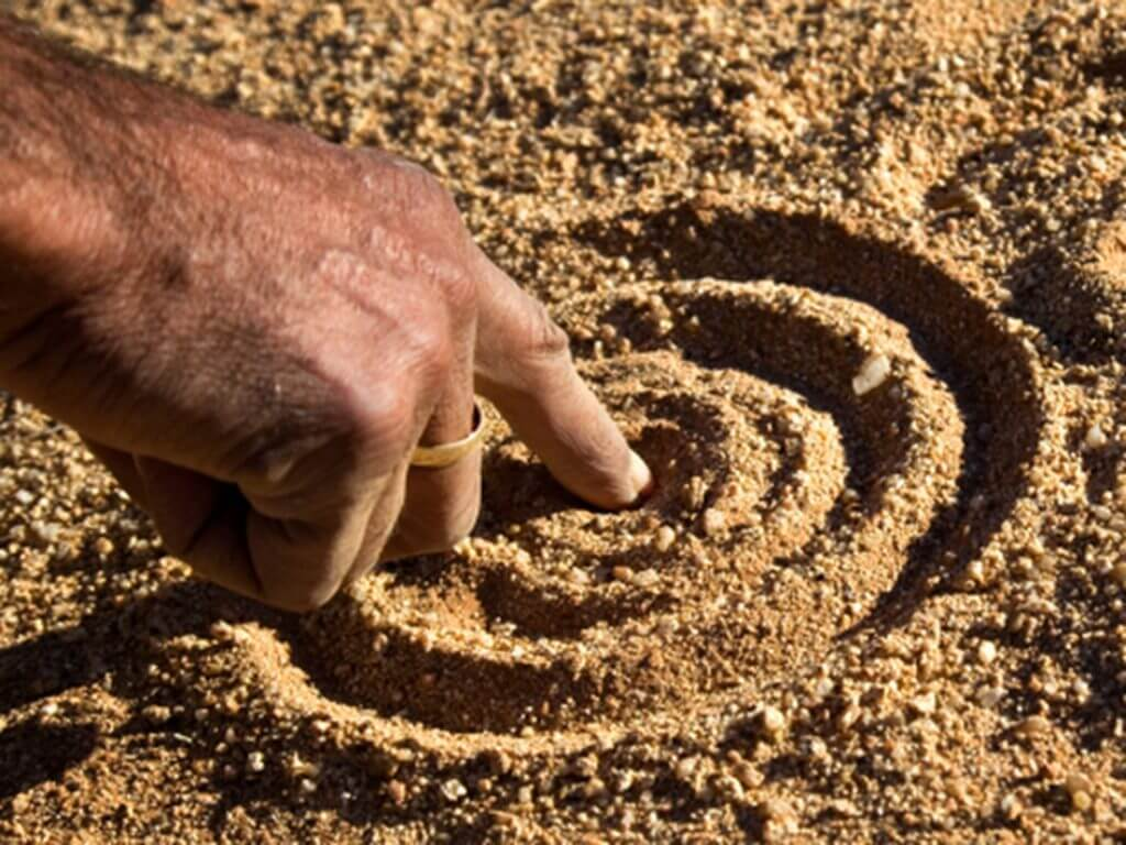 Hand drawing circle in sand